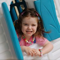 Happy-Girl-looking-out-playhouse
